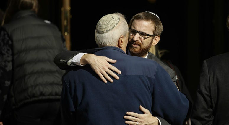 Mourners hug outside Rodef Shalom Congregation during the funeral services for brothers Cecil and David Rosenthal, Tuesday, Oct. 30, 2018, in Pittsburgh.