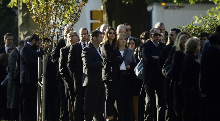 Mourners gather outside Rodef Shalom Congregation before the funeral services for brothers Cecil and David Rosenthal, Tuesday, Oct. 30, 2018, in Pittsburgh.