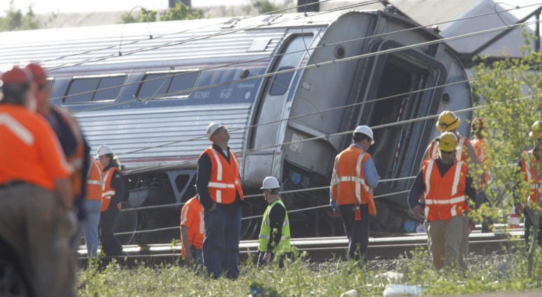 Investigators examine the train derailment site on Wednesday, May 13, 2015, after a northbound Amtrak train crashed in the Port Richmond area of Philadelphia.