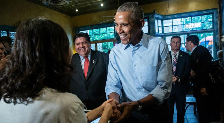 Former President Barack Obama talks to owner Young Jeon and orders food as he makes a campaign stop at Caffe Paradiso after speaking at University of Illinois in Urbana, Ill., on Sept. 7, 2018.
