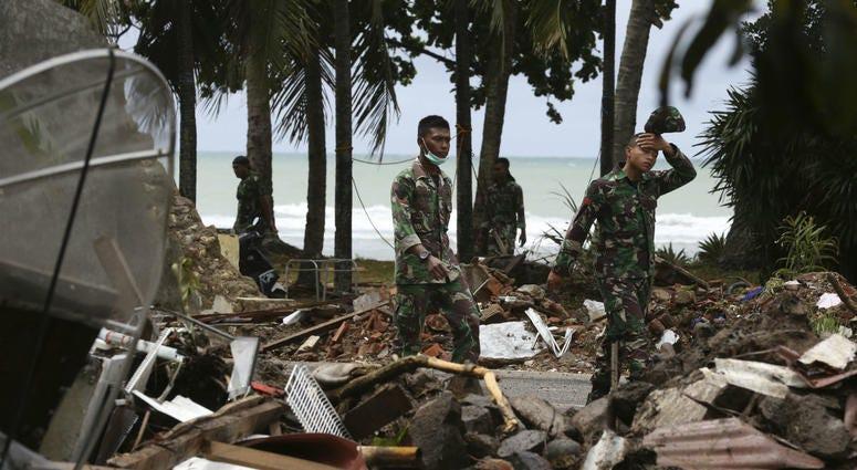 Indonesia soldier walks near debris at a tsunami-ravaged area in Carita, Indonesia, Wednesday, Dec. 26, 2018.