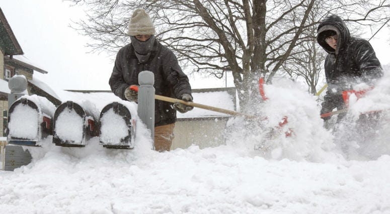 Ausencio Castaneda of Kewaskum, left, clears a path to a series of mailboxes outside a multi-family home with his son Ausencio Castaneda Jr. onMonday, Jan. 28, 2019, in Kewaskum, Wis.