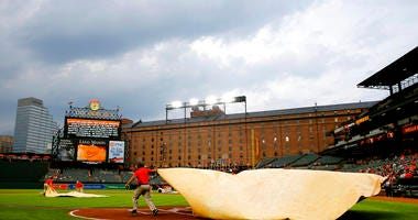 Groundskeepers cover home plate with a tarp during a rain delay
