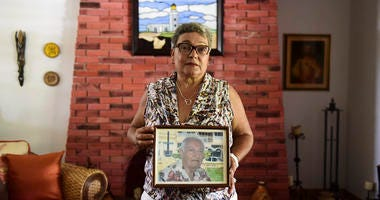 Nerybelle Perez poses with a portrait of her father, World War II veteran Efrain Perez, who died inside an ambulance after being turned away from the largest public hospital when it had no electricity or water, days after Hurricane Maria passed.