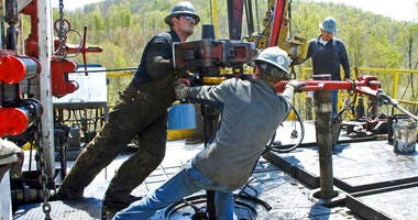 In this April 23, 2010, file photo, workers move a section of well casing into place at a Chesapeake Energy natural gas well site near the Bradford County township of Burlington, Pa.