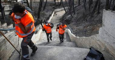 Workers carry bags with debris as clean-up operations get underway following a deadly wildfire in Mati, east of Athens, Thursday, July 26, 2018.