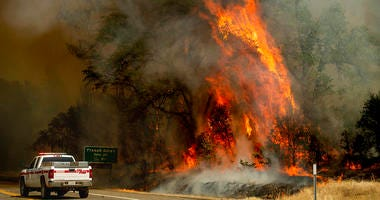 Flames from the Carr Fire lick above a Cal Fire truck in Whiskeytown, Calif., on Friday, July 27, 2018.