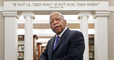U.S. Rep. John Lewis, D-Ga., poses for a photograph under a quote of his that is displayed in the Civil Rights Room in the Nashville Public Library in Nashville, Tenn.