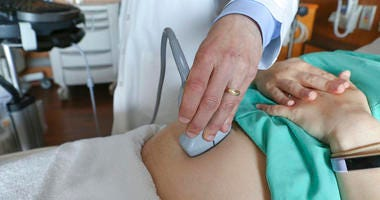 A doctor performs an ultrasound scan on a pregnant woman at a hospital in Chicago.