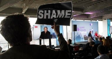 Stuart Waldman with Rise and Resist holds up a sign in silent protest as President Donald Trump's former chief strategist Steve Bannon speaks during an ideas festival sponsored by The Economist, Saturday, Sept. 15, 2018, in New York.