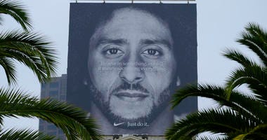 In this Sept. 5, 2018, file photo palm trees frame a large billboard on top of a Nike store that shows former San Francisco 49ers quarterback Colin Kaepernick at Union Square in San Francisco
