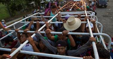 Migrants travel on a cattle truck, as a thousands-strong caravan of Central American migrants slowly makes its way toward the U.S. border, between Pijijiapan and Arriaga, Mexico, Friday, Oct. 26, 2018.