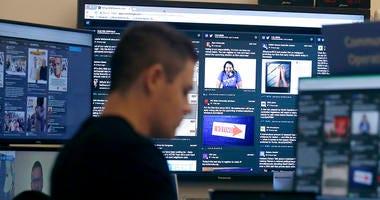 In this Oct. 17, 2018 file photo, a man works at his desk in front of monitors during a demonstration in the war room, where Facebook monitors election related content on the platform, in Menlo Park, Calif.