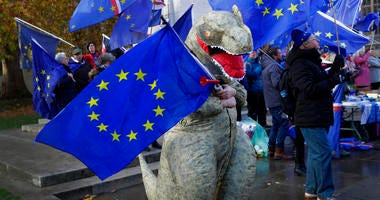 An Anti Brexit campaigner dressed a dinosaur demonstrates in Westminster in London, Monday, Nov. 19, 2018.