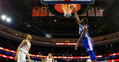 Philadelphia 76ers' Joel Embiid, right, of Cameroon, dunks the ball as New York Knicks' Kevin Knox, left, looks on during the first half of an NBA basketball game, Wednesday, Nov. 28, 2018, in Philadelphia.