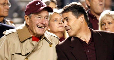 FILE - In this Nov. 26, 2009, file photo, former President George H.W. Bush, left, talks with Texas Gov. Rick Perry before an NCAA college football game between Texas and Texas A&M, in College Station, Texas.