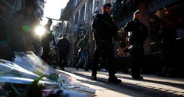 French police officers patrol in the streets front of flowers to pay respects of the victims following an attack killing three persons and wounding at least 13, in Strasbourg, eastern France, Thursday, Dec. 13, 2018.