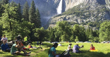 FILE - In this May 25, 2017 file photo, a class of eighth-grade students and their chaperones sit in a meadow at Yosemite National Park, Calif., below Yosemite Falls.