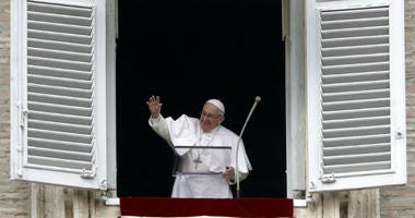 Pope Francis salutes the crowd as he recites the Angelus noon prayer from the window of his studio overlooking St.Peter's Square, at the Vatican, Sunday, Jan. 13, 2019.