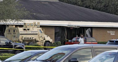 A Highlands County Sheriff's SWAT vehicle is stationed out in front of a SunTrust Bank branch, Wednesday, Jan. 23, 2019, in Sebring, Fla., where authorities say five people were shot and killed.