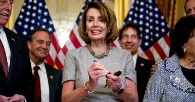 House Speaker Nancy Pelosi of Calif., accompanied by House Democratic members stand after signs a deal to reopen the government on Capitol Hill in Washington, Friday, Jan. 25, 2019.