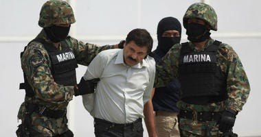 """Joaquin """"El Chapo"""" Guzman, center, is escorted to a helicopter in handcuffs by Mexican navy marines."""