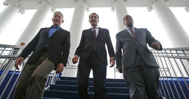FILE - In this Jan. 12, 2018 file photo, Virginia Gov.-elect, Lt. Gov Ralph Northam, center, walks down the reviewing stand with Lt. Gov-elect, Justin Fairfax, right, and Attorney General Mark Herring at the Capitol in Richmond, Va.