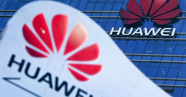 FILE - This Dec. 18, 2018, file photo, shows company signage on display near the Huawei office building at its research and development center in Dongguan, in south China's Guangdong province.