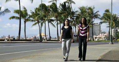 Diane Cervelli, left, and Taeko Bufford, right, walk past Waikiki beach in Honolulu.