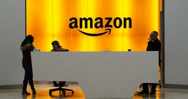 People stand in the lobby for Amazon offices in New York.