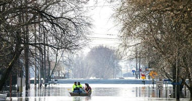 People on a boat float down floodwaters that cover Washington Street in Hamburg, Iowa.