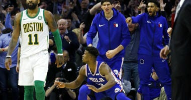 Philadelphia 76ers' Jimmy Butler, center, celebrates after scoring a basket against Boston Celtics' Kyrie Irving during the second half of an NBA basketball game Wednesday, March 20, 2019, in Philadelphia. Philadelphia won 118-115.
