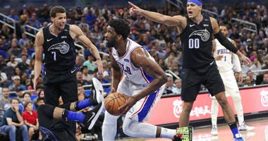 Philadelphia 76ers' Joel Embiid, center, is called for a charge as he runs into Orlando Magic's Khem Birch, lower left, as Magic's Michael Carter-Williams (7) and Aaron Gordon (00) look on during the first half of an NBA basketball game.