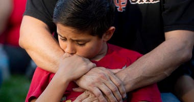 Robbie Ramirez, 10, holds onto his father, Robert Ramirez, during a vigil for victims of a Sunday evening shooting that left three people dead at the Gilroy Garlic Festival, Monday, July 29, 2019, in Gilroy, Calif.