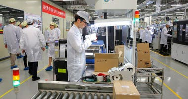 A staff member works on a mobile phone production line during a media tour in Huawei factory in Dongguan, China's Guangdong province.