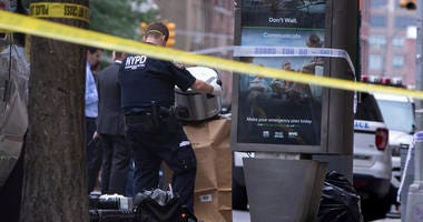 An investigator bags a suspicious package as evidence after it was thought to be an explosive device in Manhattan's Chelsea neighborhood Friday, Aug. 16, 2019, in New York.