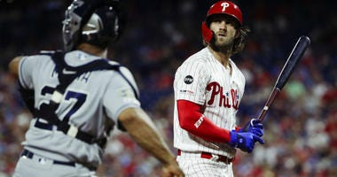 Philadelphia Phillies' Bryce Harper, right, looks up after striking out during the eighth inning of a baseball game against the San Diego Padres, Saturday, Aug. 17, 2019, in Philadelphia.