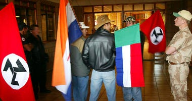 "In this June 11 2004, file photo, supporters of the Afrikaner Resistance Movement (AWB) display an old South African flag, second from left, an old Afrikaner ""Vierkleur"" flag and swastika-like flags."