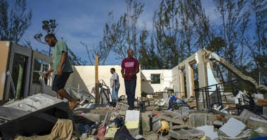 People walk through the remains of a home in the Bahamas.