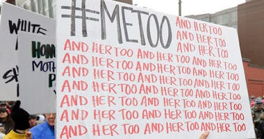 A demonstrator carries a sign with the popular Twitter hashtag #MeToo used by people speaking out against sexual harassment as she takes part in a Women's March in Seattle.