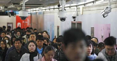 Commuters walk by surveillance cameras installed at a walkway in between two subway stations in Beijing.