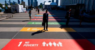 People walk along a plaza at United Nations Headquarters Saturday, Sept. 21, 2019.