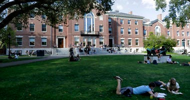 People rest on grass while reading at Brown University in Providence, R.I.