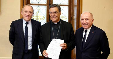 Francois-Henri Pinault, CEO of French luxury group Kering, left, his father Francois Pinault, right, and Archbishop of Paris Michel Aupetit, center, pose after signing an agreement to raise money for the rebuild of Notre-Dame cathedral, in Paris.