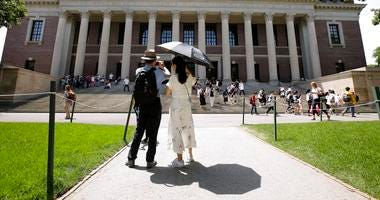 People stop to record images of Widener Library on the campus of Harvard University in Cambridge, Mass.