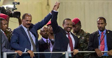 Eritrean President Isaias Afwerki, second left, and Ethiopia's Prime Minister Abiy Ahmed, center, hold hands as they wave at the crowds in Addis Ababa, Ethiopia.