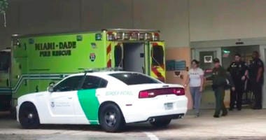 A border patrol agents escorts a woman to a patrol car Sunday, Oct. 13, 2019, at Aventura Hospital in Aventura, Fla. The woman had been detained by border patrol agents, when she fell ill.
