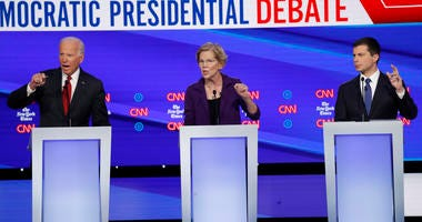 Democratic presidential candidate former Vice President Joe Biden, left, Sen. Elizabeth Warren, D-Mass., center and South Bend Mayor Pete Buttigieg speak during a Democratic presidential primary debate hosted by CNN/New York Times.