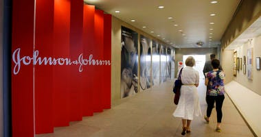 People walk along a corridor at the headquarters of Johnson & Johnson in New Brunswick, N.J.