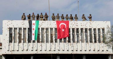 Turkish soldiers, right, and Turkey-backed opposition fighters stand atop a building next to their flags in Syrian town of Ras al Ayn, northeastern Syria, Wednesday, Oct. 23, 2019.
